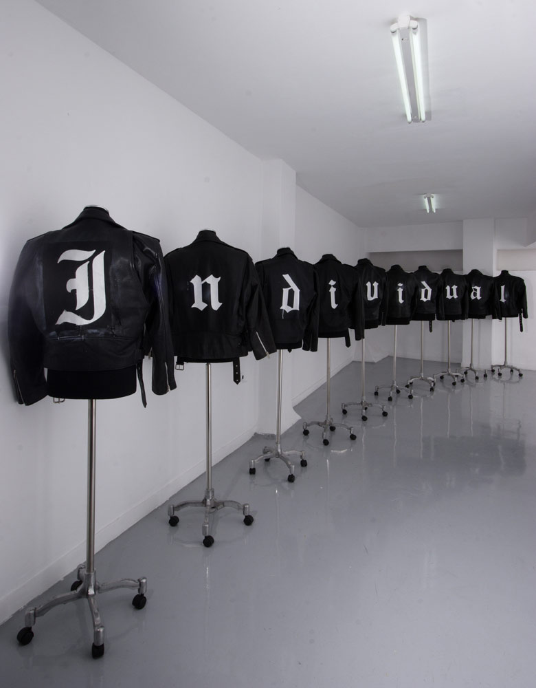 The installation consists of ten showroom dummies dressed up with leather jackets that the artist spray-painted with single letters composing the word
